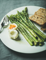 Cooked asparagus with soft-boiled egg, grilled bread toasts and herbs