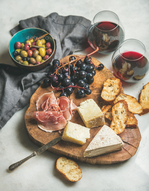 Wine and snack set on wooden board over grey background - Stock Photo - Images