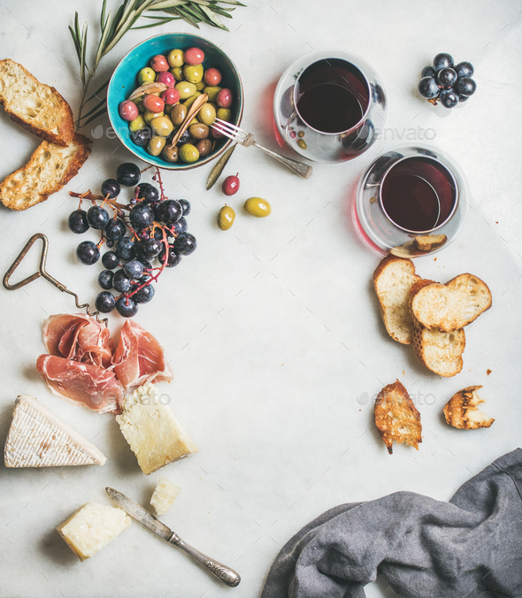 Cheese, olives, grapes, prosciutto, baguette and red wine, top view - Stock Photo - Images