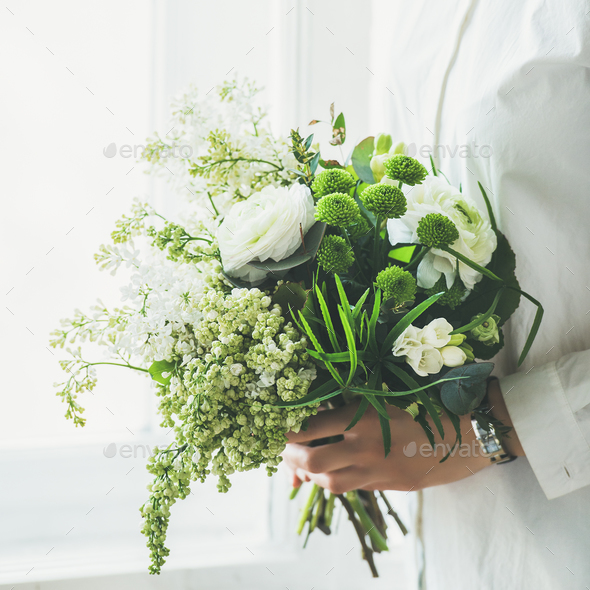 Young woman wearing white clothes holding flowers bouquet. Wedding concept - Stock Photo - Images