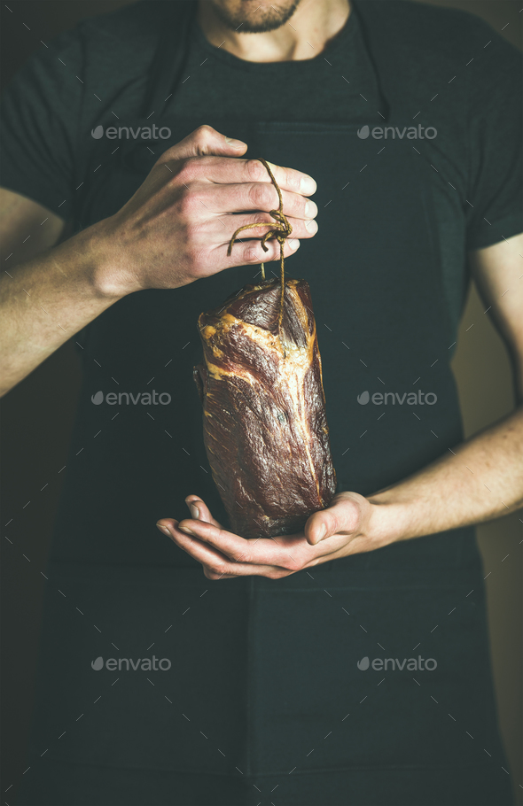 Man in black apron keeping cut of cured pork - Stock Photo - Images