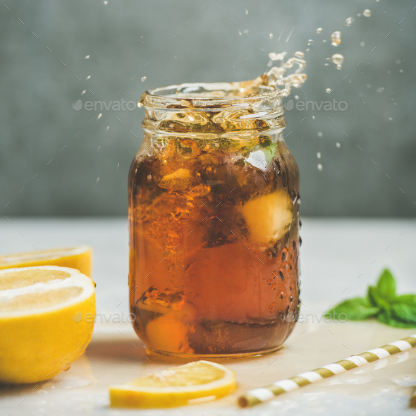 Iced tea with fresh herbs in jar with splashes - Stock Photo - Images