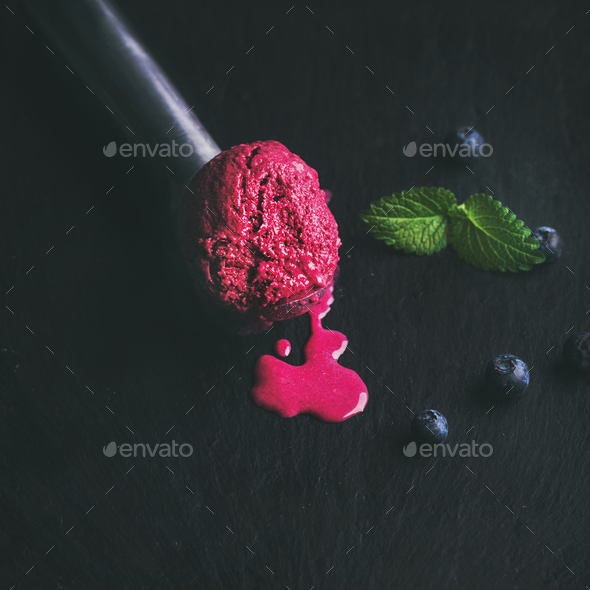Melting scoop of blueberry ice-cream with fresh mint leaves - Stock Photo - Images