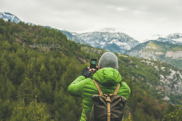 Young man traveller making photo of mountains and green slopes - Stock Photo - Images
