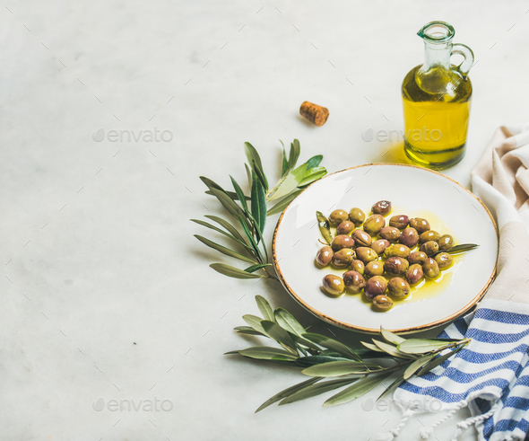 Pickled green Mediterranean olives, olive tree branch and virgin oil - Stock Photo - Images