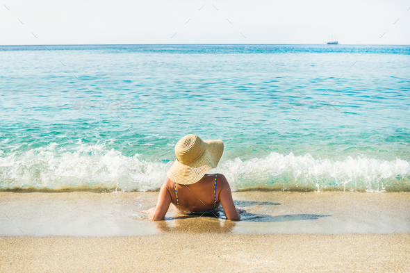 Woman lying on sand and enjoying clear blue sea waters - Stock Photo - Images