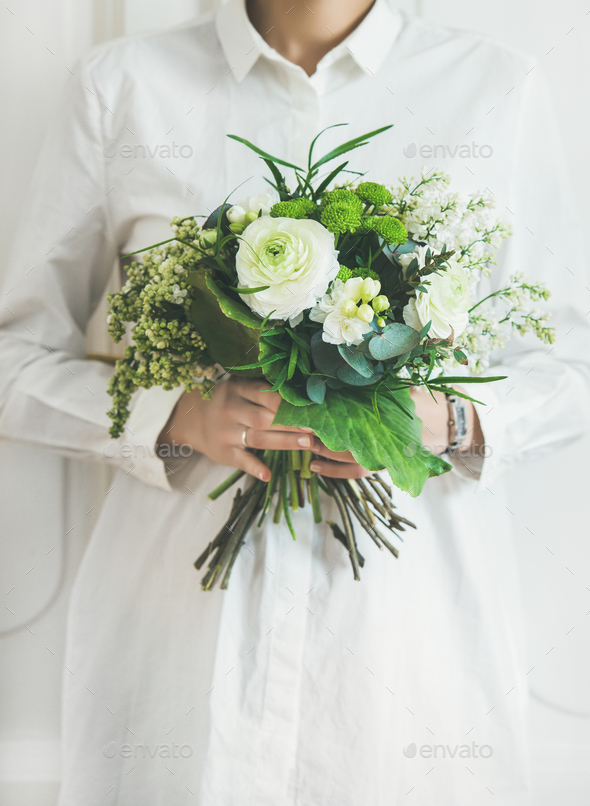 Young woman wearing white clothes holding bouquet. Flower shop concept - Stock Photo - Images