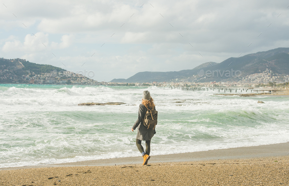 Young woman looking at stormy Mediterranean sea, Alanya, Turkey - Stock Photo - Images