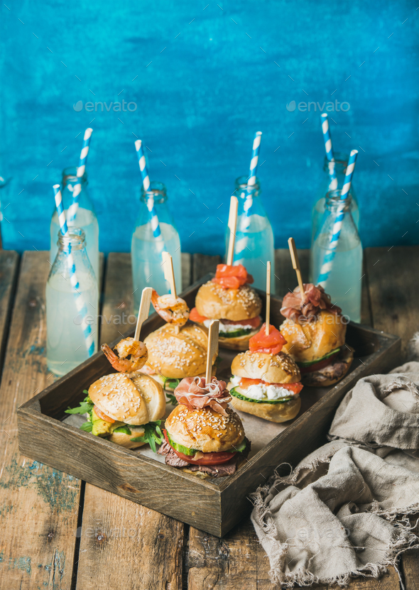Homemade burgers in wooden tray and lemonade in bottles - Stock Photo - Images