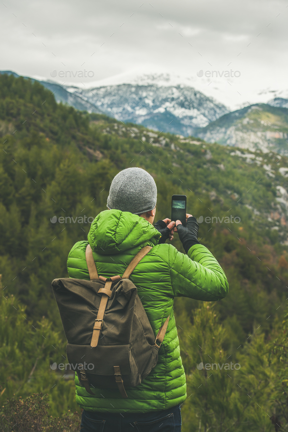 Young man traveller making photo of green valley and slopes - Stock Photo - Images
