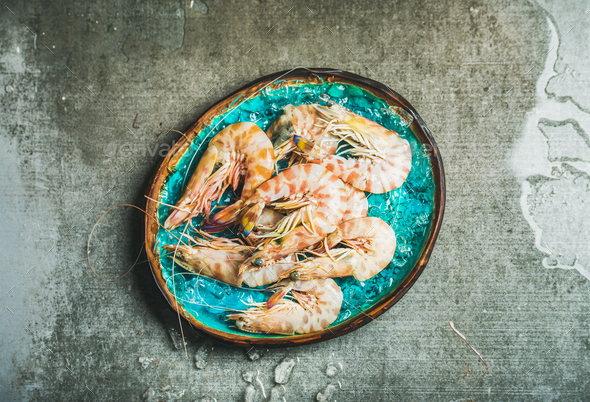 Raw uncooked tiger prawns on chipped ice, copy space - Stock Photo - Images