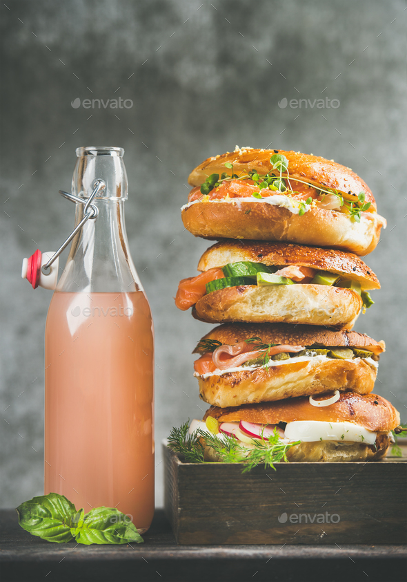 Heap of bagels with salmon, eggs, vegetables, capers, cream-cheese, lemonade - Stock Photo - Images