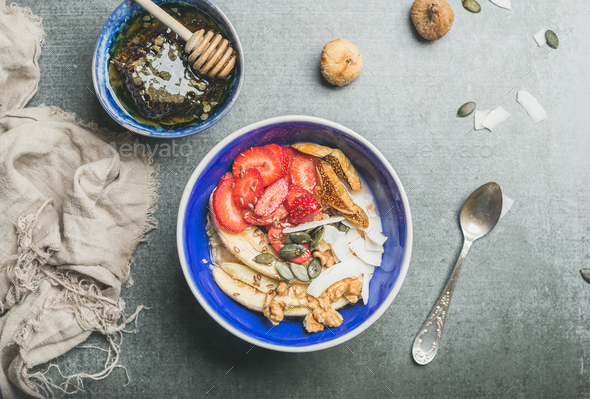 Yogurt, granola, seeds, berry and honey in blue ceramic bowl - Stock Photo - Images