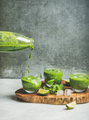 Fresh smoothie with ice, mint and lime pouring from bottle