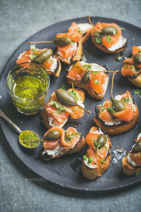 Homemade Italian salmon crostini in black plate over grey background - Stock Photo - Images