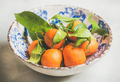 Freshly picked mandarines with leaves in plate over light background