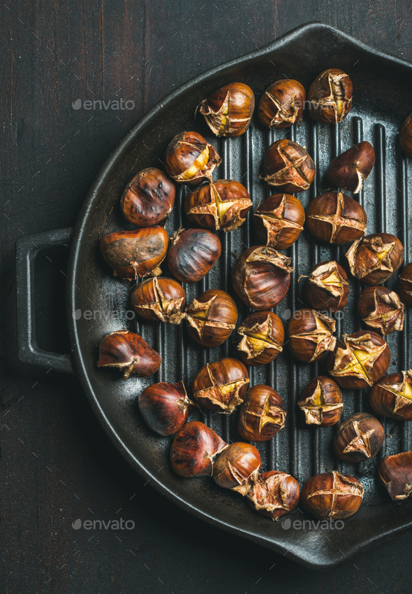 Roasted chestnuts in grilling pan over dark wooden background - Stock Photo - Images