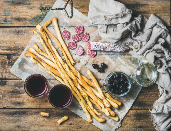 Grissini bread sticks, sausage, olives and red wine, wooden background - Stock Photo - Images