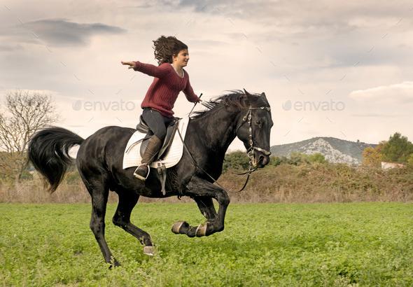 riding girl and black stallion - Stock Photo - Images