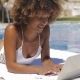 Woman Typing Laptop on Poolside