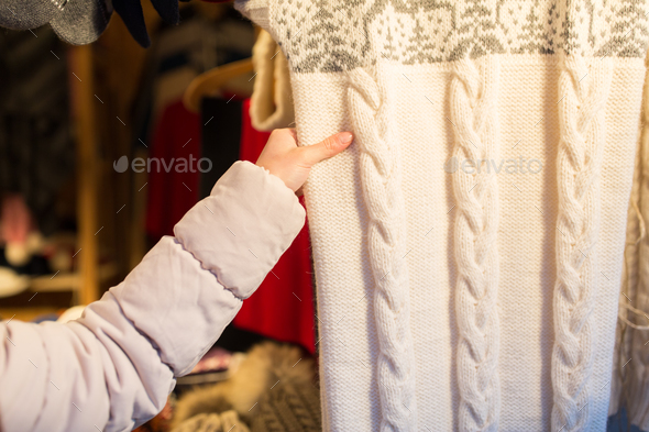 woman buying woolen clothes at christmas market - Stock Photo - Images