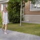 Charming Cheerful Woman in Casual Dress Walking Along Sidewalk and Looking at Camera