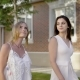 Two Young Girls in White Summer Dresses Walking Down Street and Looking Away Dreamly