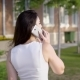 Back View of Anonymous Brunette in White Talking Smartphone on Background of Street in Summer