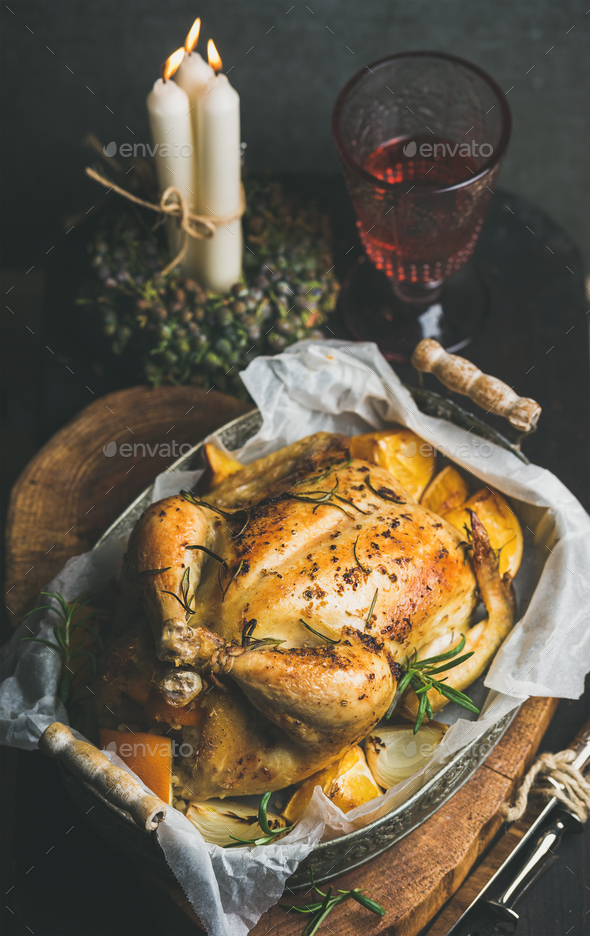 Christmas table set with oven roasted whole chicken and wine - Stock Photo - Images
