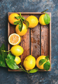 Freshly picked lemons with leaves in wooden tray