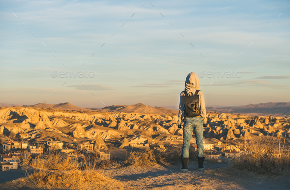 Young woman traveller in hoodie watching sunrise, Cappadocia, Central Turkey - Stock Photo - Images