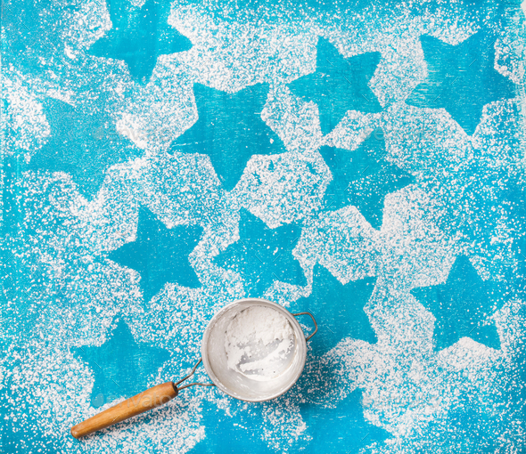 Sieve with sugar powder over bright blue background - Stock Photo - Images