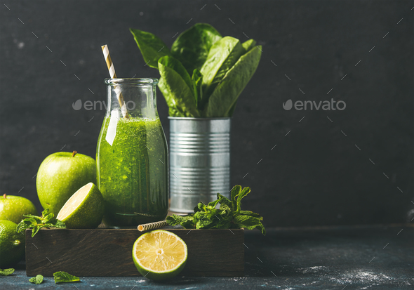 Green smoothie in glass bottle with fresh fruits, copy space - Stock Photo - Images