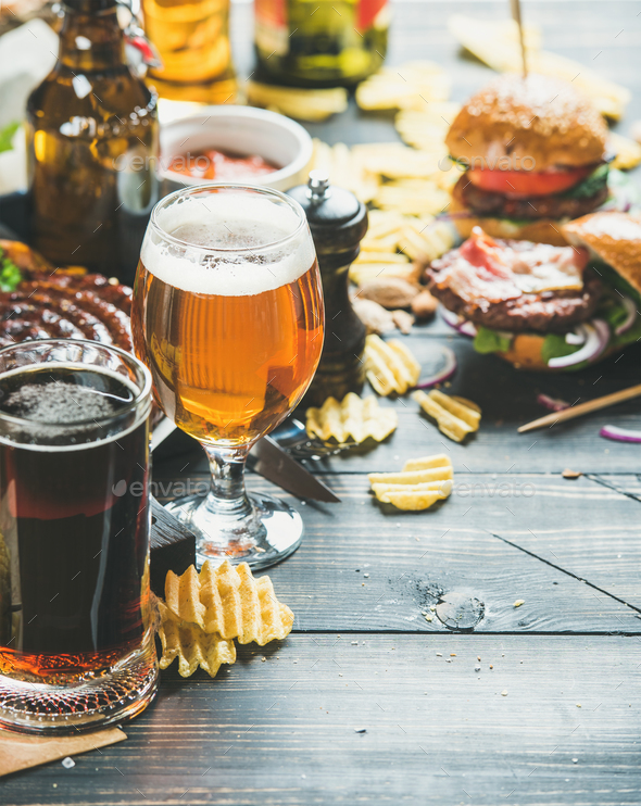 Beer and snack variety on dark wooden scorched background - Stock Photo - Images