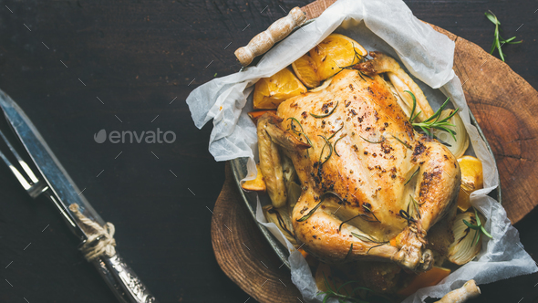 Roasted chicken with oganges, bulgur, rosemary over dark background - Stock Photo - Images
