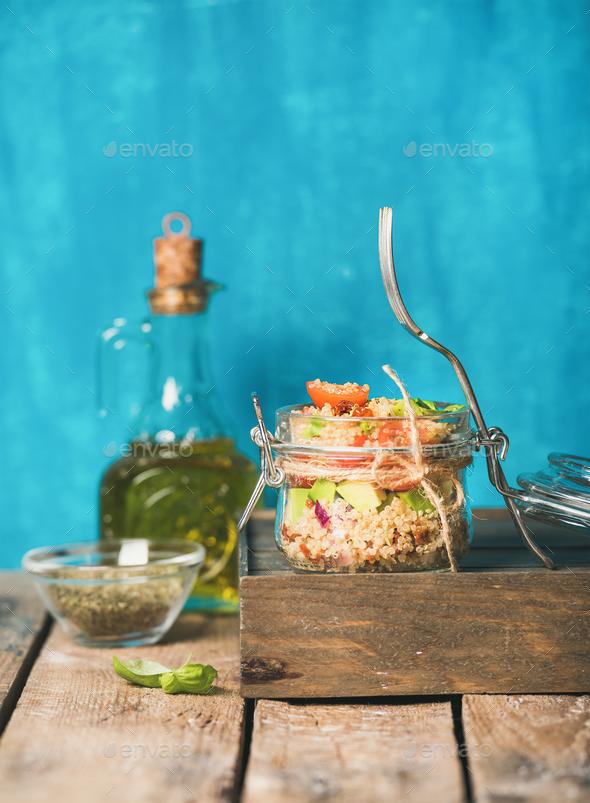 Healthy homemade jar quinoa salad with tomatoes, avocado, fresh basil - Stock Photo - Images