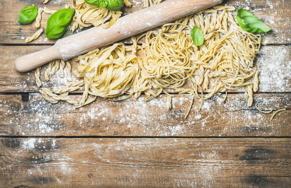 Various homemade fresh uncooked Italian pasta on wooden background - Stock Photo - Images