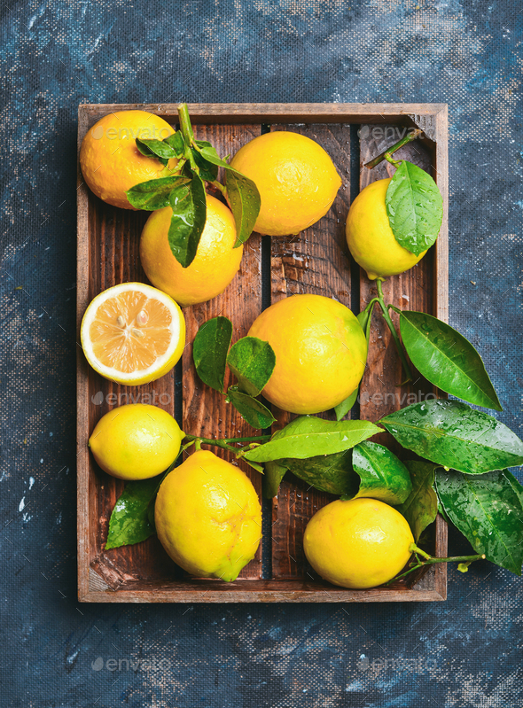 Freshly picked lemons with leaves in rustic wooden tray - Stock Photo - Images