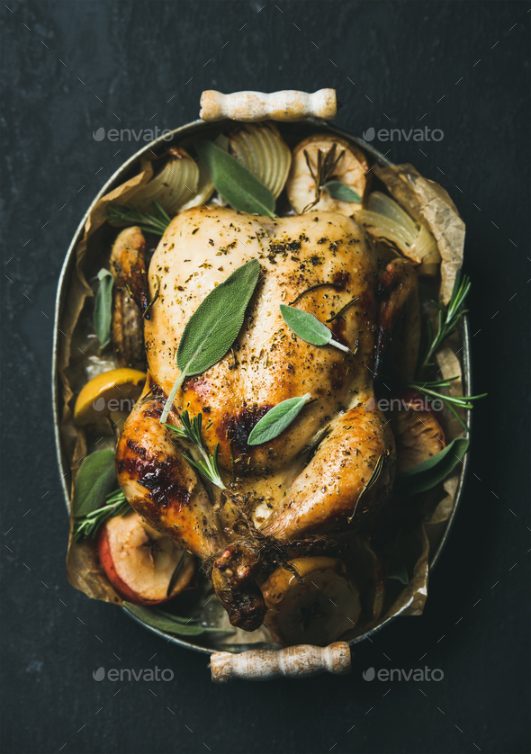 Oven roasted whole chicken with fresh sage leaves and apples - Stock Photo - Images