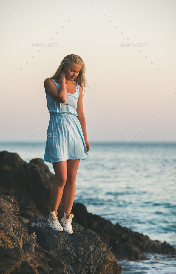Young blond woman standing near sea and looking down, Turkey - Stock Photo - Images