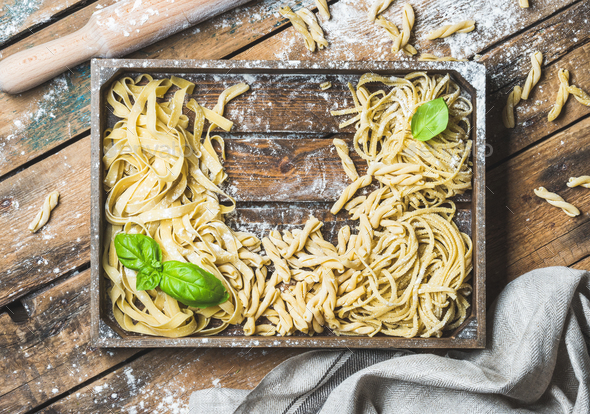 Various uncooked Italian pasta in wooden tray with basil leaves - Stock Photo - Images