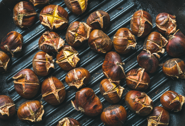 Roasted chestnuts over black cast iron grilling pan surface - Stock Photo - Images