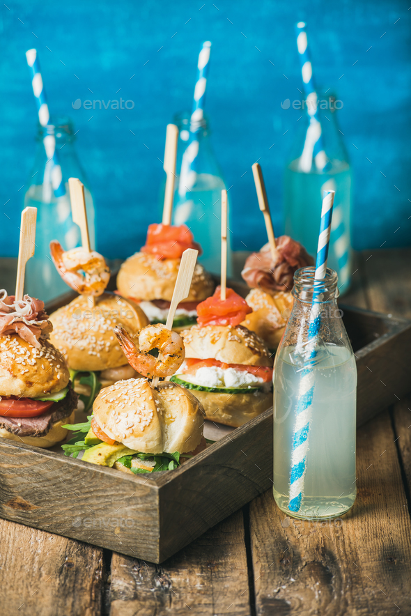 Different homemade burgers with sticks in wooden tray and lemonade - Stock Photo - Images