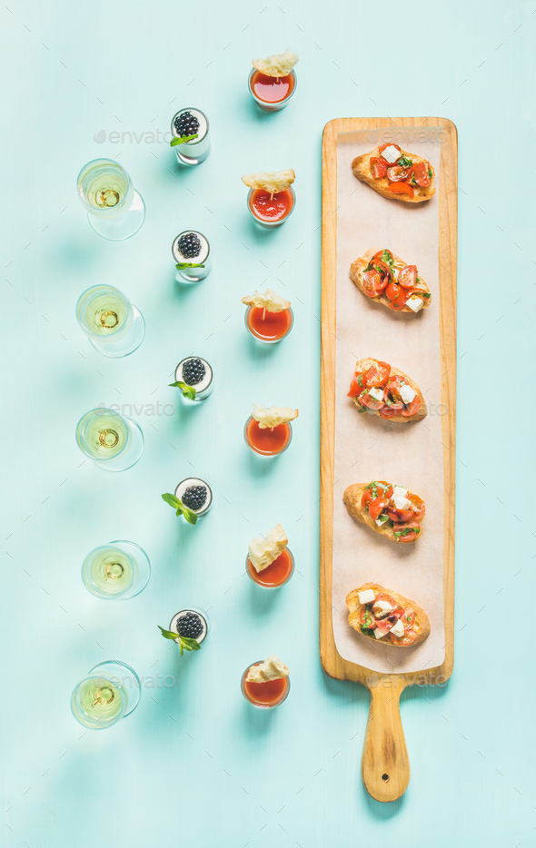 Snacks, brushettas, gazpacho shots, desserts, champagne over pastel blue background - Stock Photo - Images