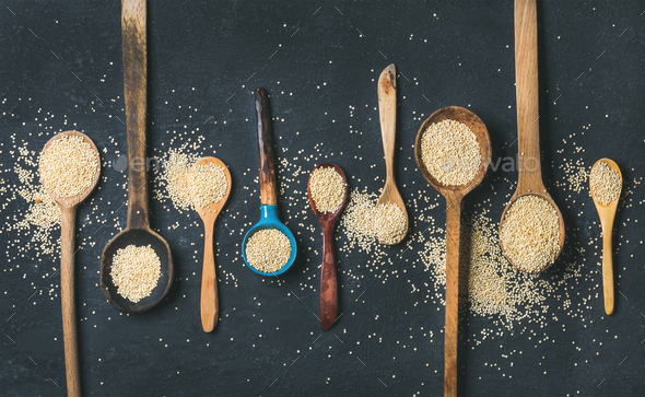 Quinoa seeds in different spoons over black stone background - Stock Photo - Images