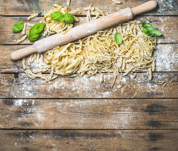 Various homemade fresh uncooked Italian pasta and plunger - Stock Photo - Images