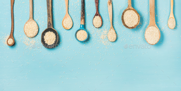 Quinoa seeds in different spoons over light blue background - Stock Photo - Images