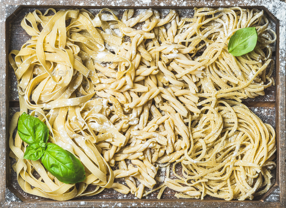 Uncooked Italian pasta in wooden tray with basil and flour - Stock Photo - Images