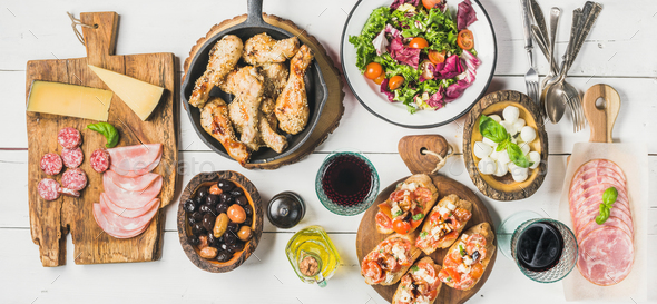 Rustic table set with chicken, salad, different snacks and wine - Stock Photo - Images
