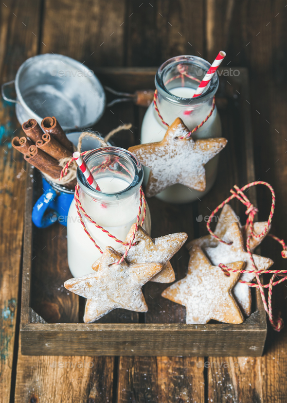 Bottles with milk for Santa and Christmas homemade gingerbread biscuits - Stock Photo - Images